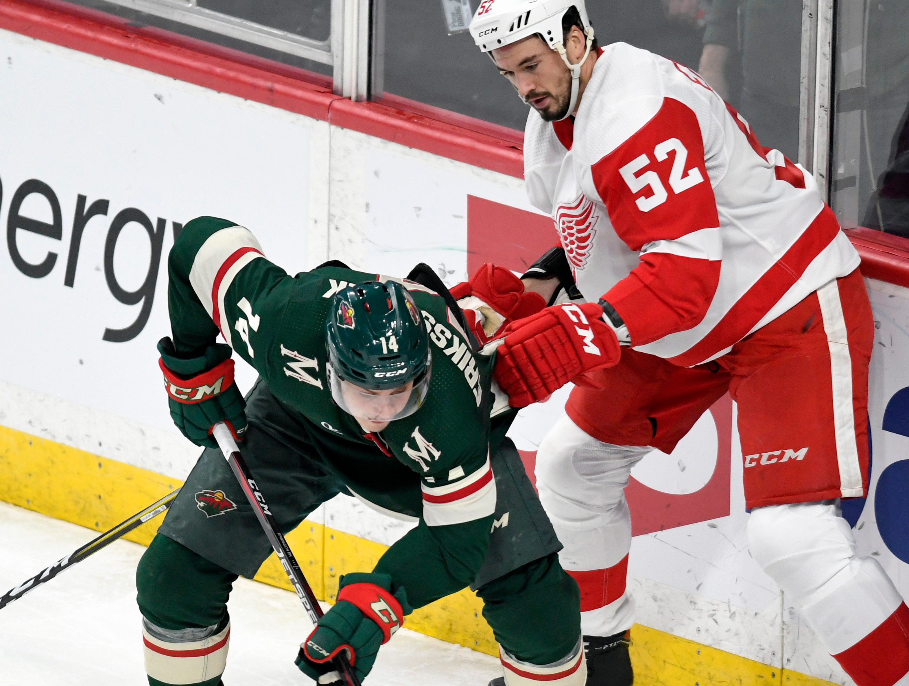 Minnesota Wild's Joel Eriksson Ek, left, of Sweden, takes the puck away from Detroit Red Wings' Jonathan Ericsson (52), of Sweden, during the second period of an NHL hockey game Saturday, Jan. 12, 2019, in St. Paul, Minn. (AP Photo/Tom Olmscheid)