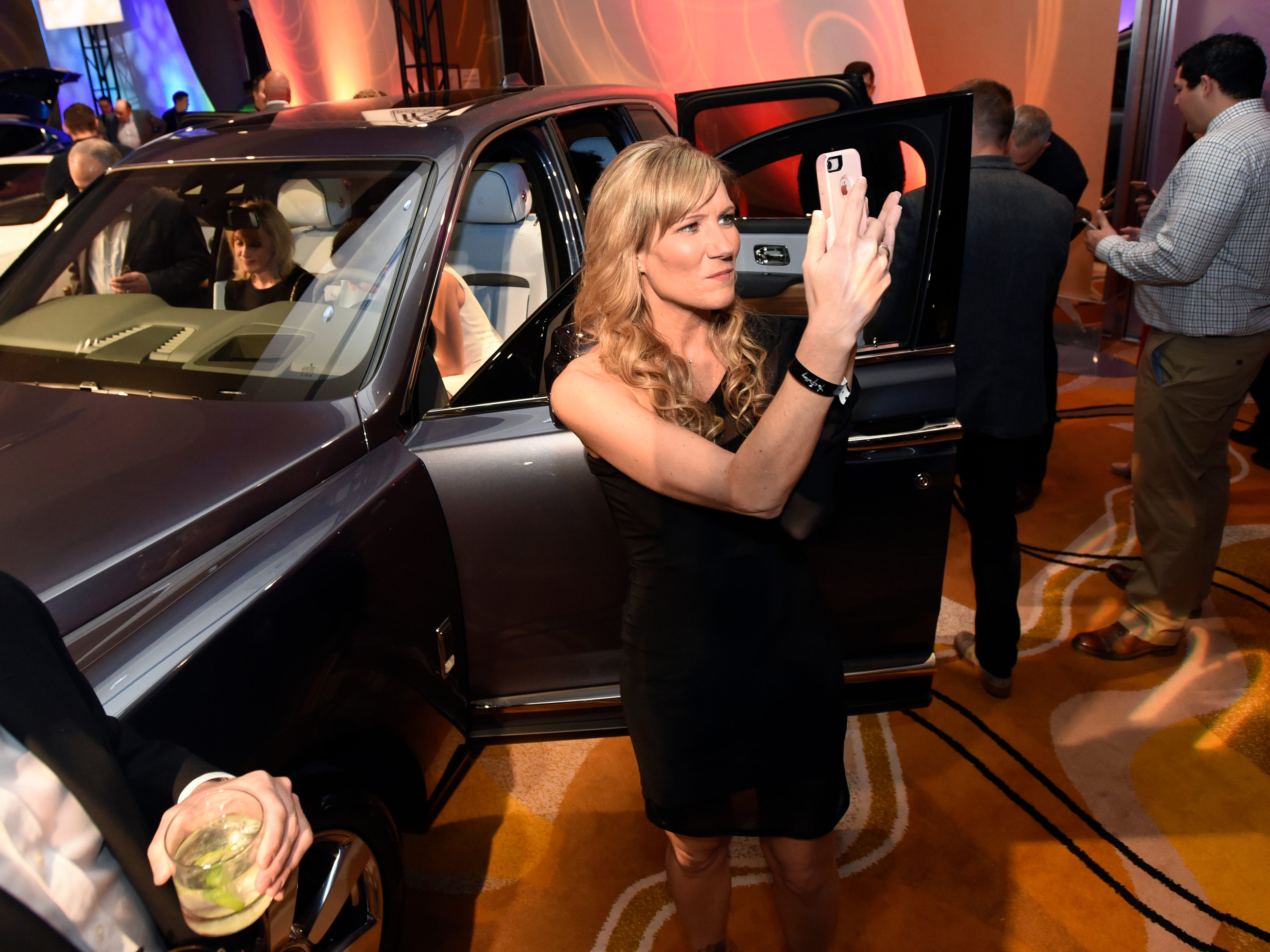 Erin Steen of Byron Center, Michigan, takes a selfie next to the Rolls-Royce Cullinan SUV.