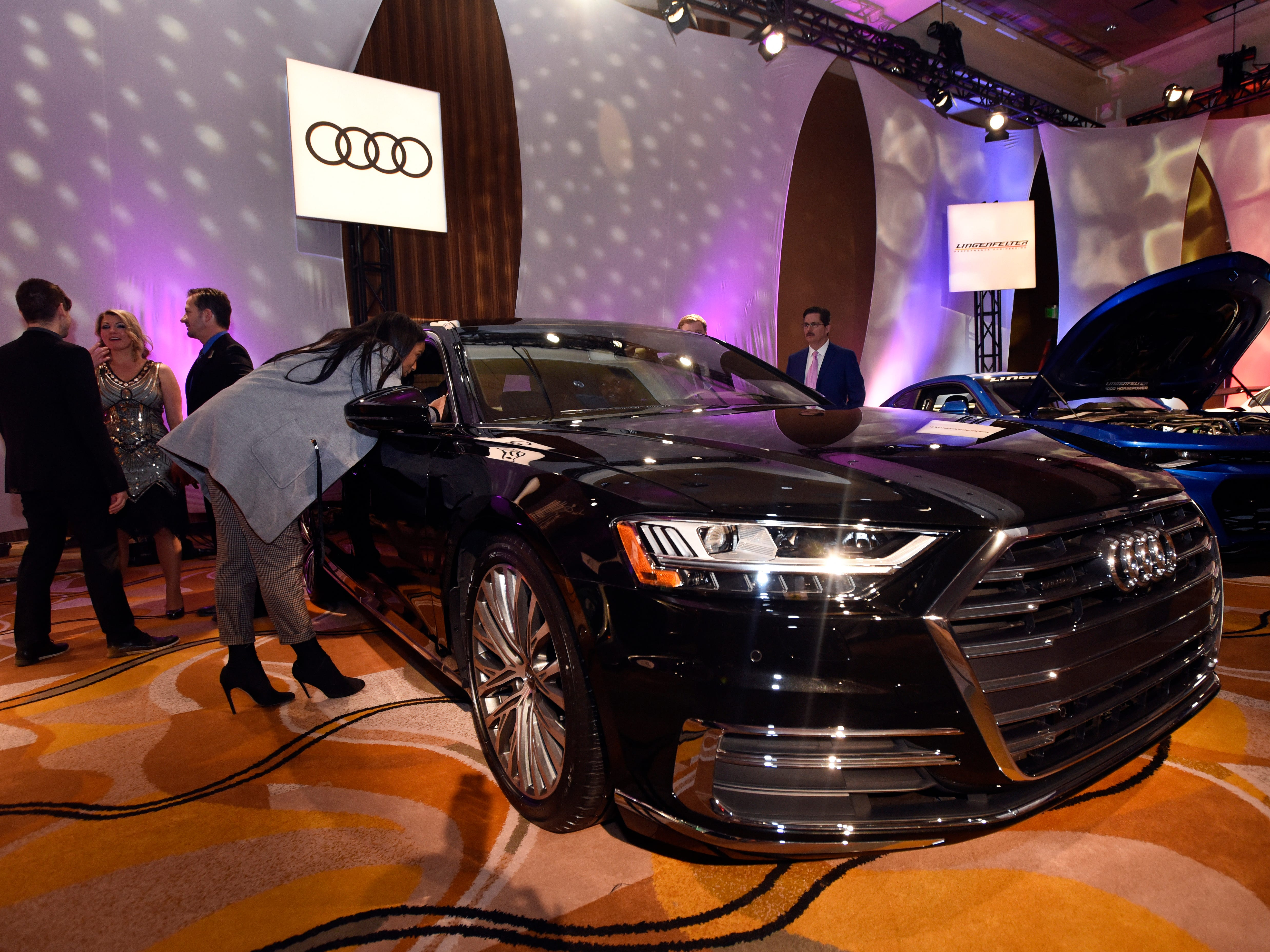 Attendees look over luxury vehicles, such as this Audi, at The Gallery.
