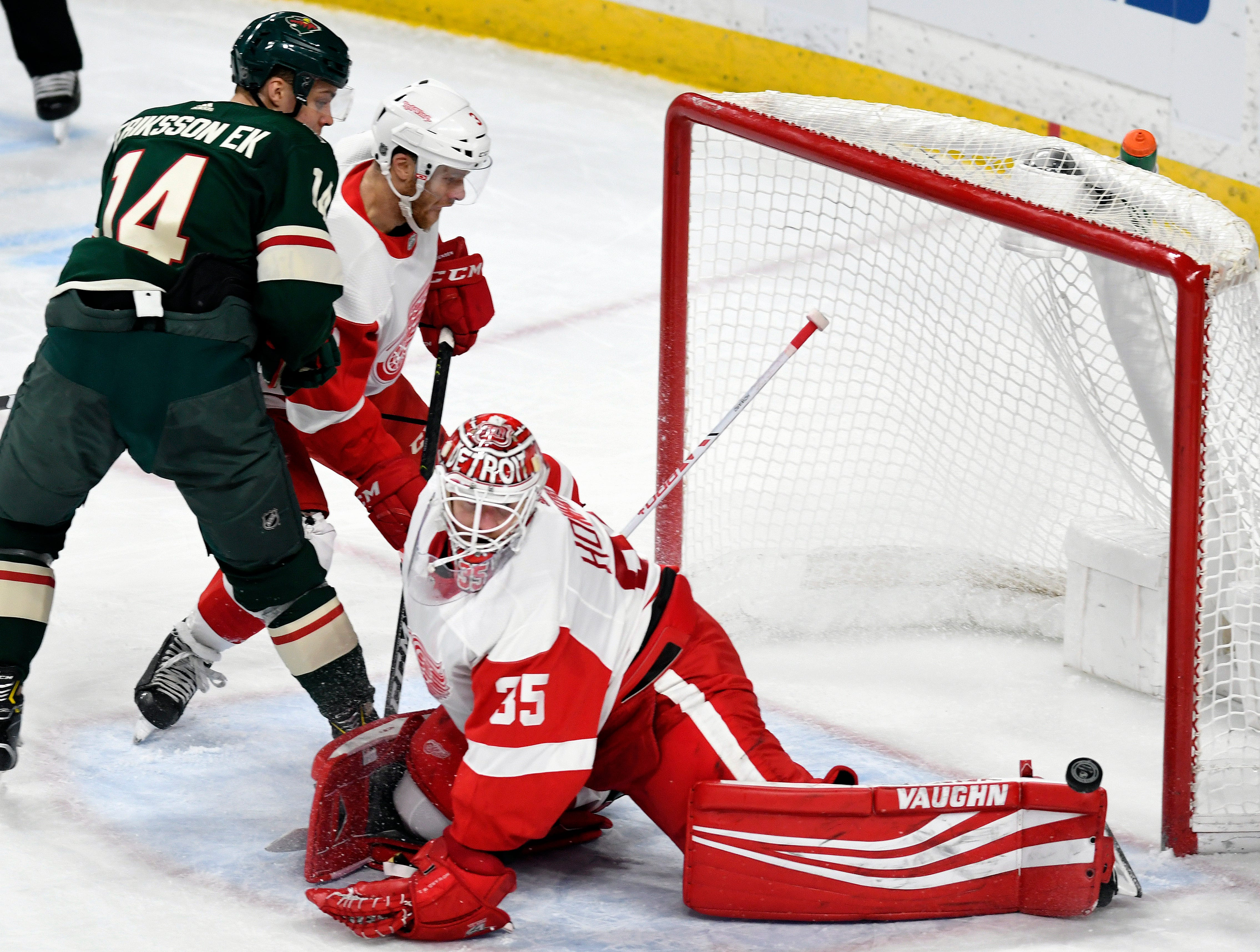 Detroit Red Wings goalie Jimmy Howard (35) has the puck roll off the end of his pad as the Red Wings' Nik Jensen, center, holds Minnesota Wild's Joel Eriksson Ek (14), of Sweden, away from the goal during the second period of an NHL hockey game Saturday, Jan. 12, 2019, in St. Paul, Minn. (AP Photo/Tom Olmscheid)