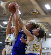 Castle's Natalie Niehaus (32) and Mikele Niehaus (12) fight Memorial's Peyton Murphy (12) for the rebound during the SIAC tournament championship at Reitz High School in Evansville, Ind., Saturday, Jan. 12, 2019.