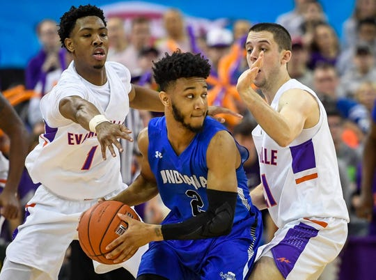Indiana State's Jordan Barnes (2) looks to pass under defense pressure from University of Evansville's Marty Hill (1) and Shea Feehan (21) as the University of Evansville Purple Aces play the Indiana State Sycamores at the Evansville Ford Center Saturday, January 12, 2019.