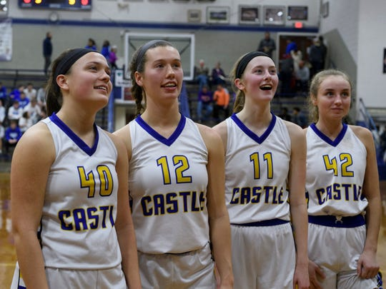 Castle's Mckenna Tutt (40), Mikele Niehaus (12), Carly Harpenau (11) and Josie Freeman (42) watch their teammates cut pieces of the game winning net after claiming the SIAC championship title at Reitz High School in Evansville, Ind., Saturday, Jan. 12, 2019. The Knights defeated the Tigers 49-31 to win the SIAC tournament for the second straight season.