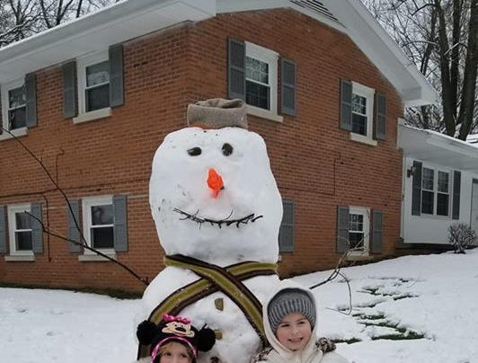 Millie and Lucy Voegel pose with the giant snowman they created at their family's Evansville home.