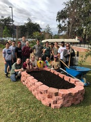 Student volunteers celebrate the first built garden bed.
