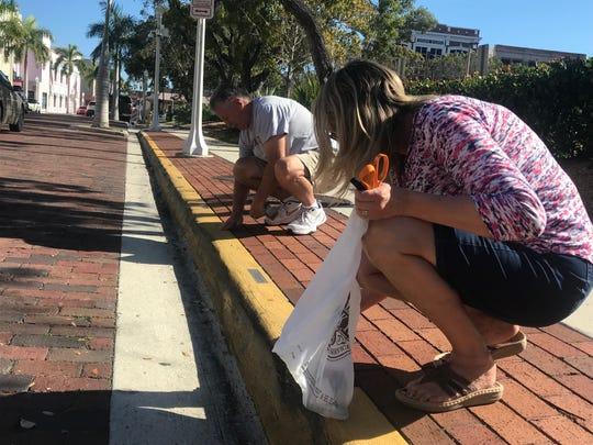"Frank and Diane Crater of North Fort Myers re-tape a viewing spot for the Edison Festival of Light Grand Parade on Sunday. The Craters had originally selected a spot on Monroe Street unaware that a change in the parade route was being made. ""It didn't bother us, it was just kind of a surprise,"" Frank Crater said."