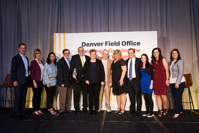 Bill Himmelberg (fifth from left in yellow tie) stands with his family to accept an award at a recent corporate gathering for McDonald's employees in Denver.