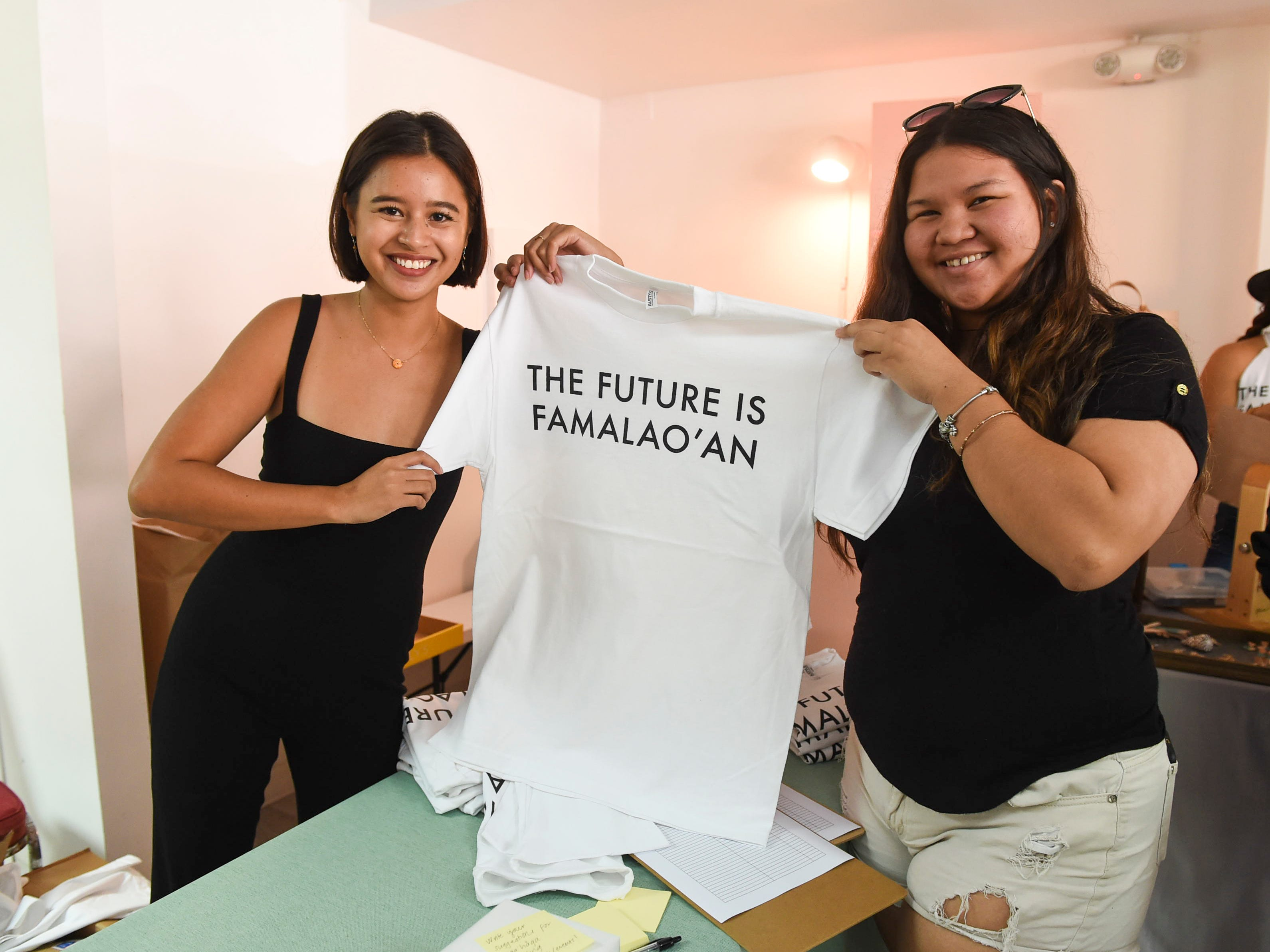 "Chauntae Quichocho, right, holds a newly purchased ""The Future is Famalao'an"" shirt  with Maga'håga Rising co-founder, Chloe Babauta, during a launch party at Sundays Guam in Tumon, Jan. 13, 2018."