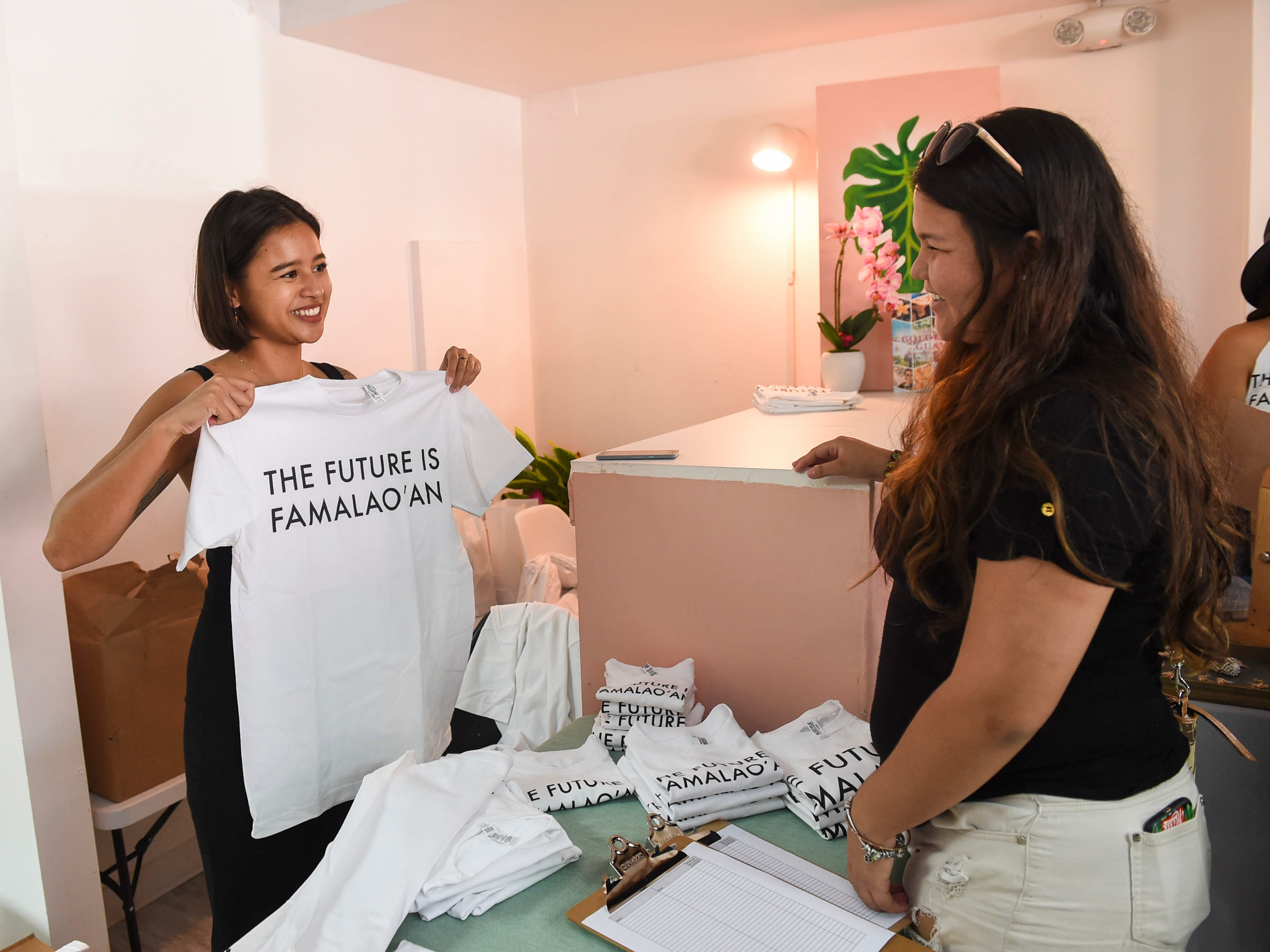 Chloe Babauta, left, co-founder of women's group, Maga'håga Rising, makes a T-shirt sale, during her organization's launch party at Sundays Guam in Tumon, Jan. 13, 2018.
