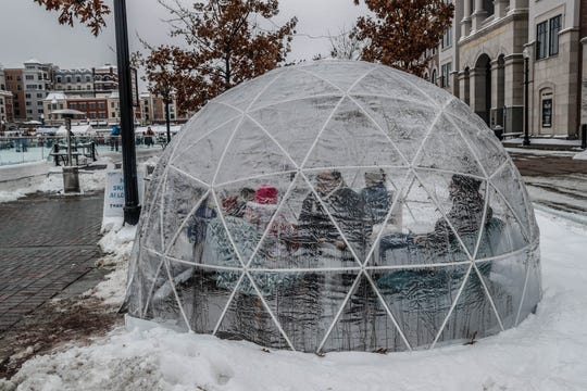 Guests keep warm in a heated igloo at the second annual Carmel Festival of Ice, held at Center Green in Carmel Ind. on Sunday, Jan. 13, 2019.