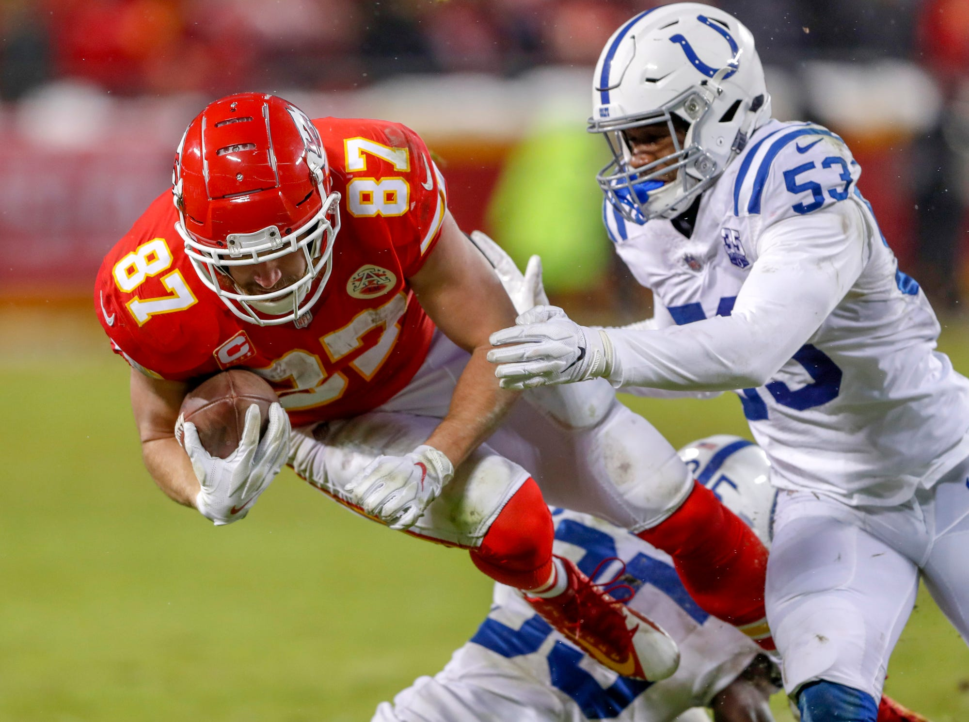 Kansas City Chiefs tight end Travis Kelce (87) gets the first down and is brought down shortly after by Indianapolis Colts outside linebacker Darius Leonard (53) and cornerback Pierre Desir (35)  in the third quarter at Arrowhead Stadium in Kansas City, Mo., on Saturday, Jan. 12, 2019.