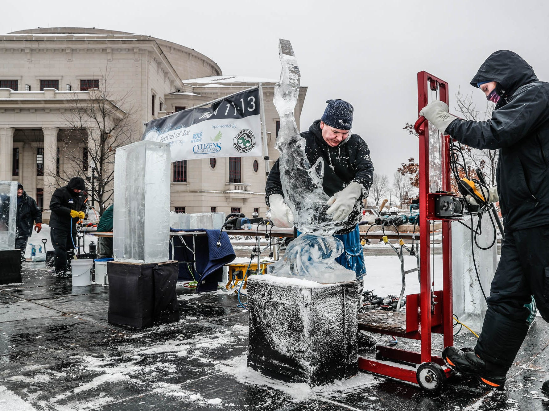 "Sculptors Stephan Koch,center right, is assisted in moving his first round winning sculpture from a speed ""carve off"" which took place during the second annual Carmel Festival of Ice, held at Center Green in Carmel Ind. on Sunday, Jan. 13, 2019."