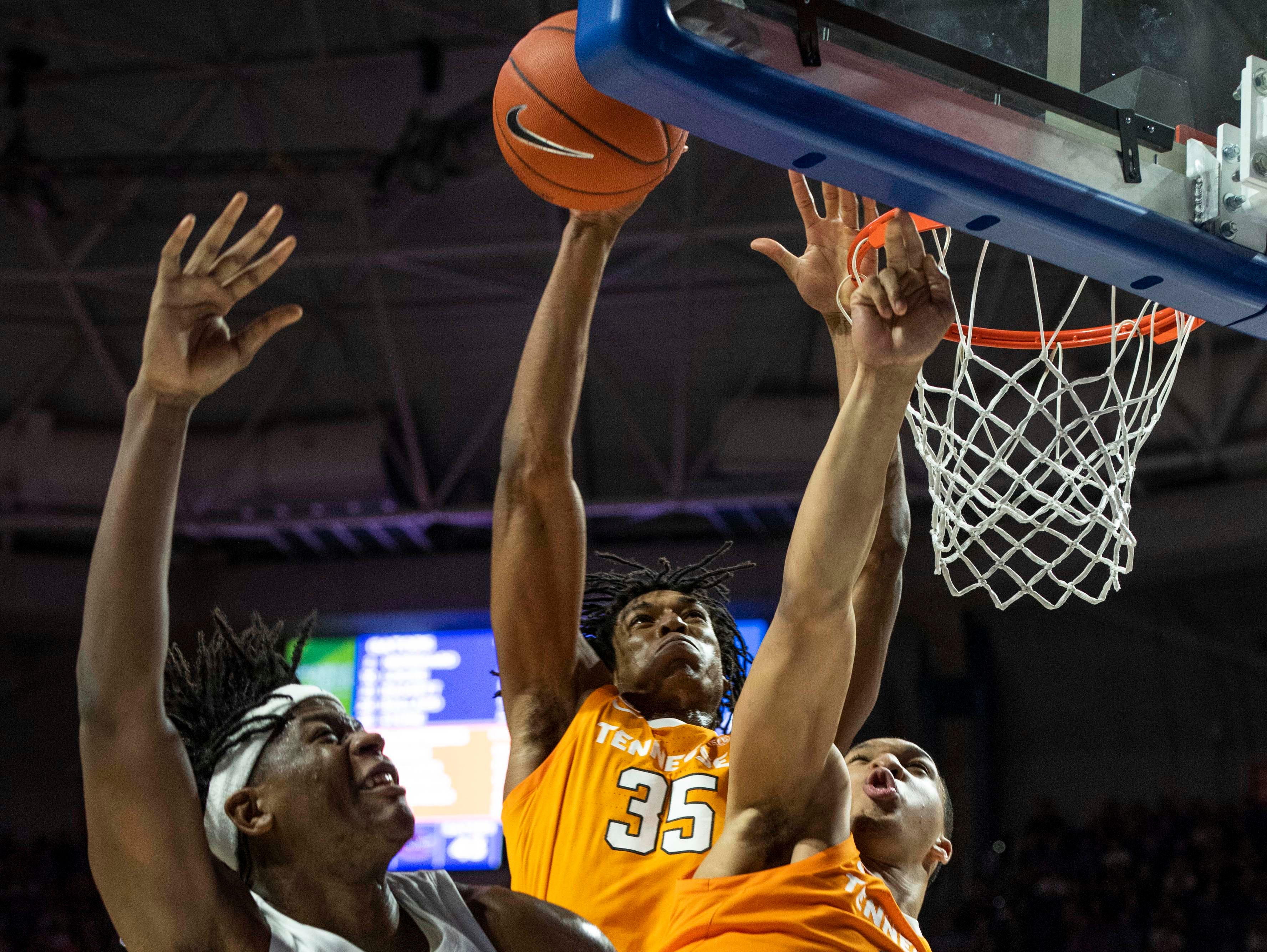 Florida Gators forward Dontay Bassett (21) drives for the net as Tennessee Volunteers forward Grant Williams (2) and forward Yves Pons (35) defend  on Jan. 12, 2019.