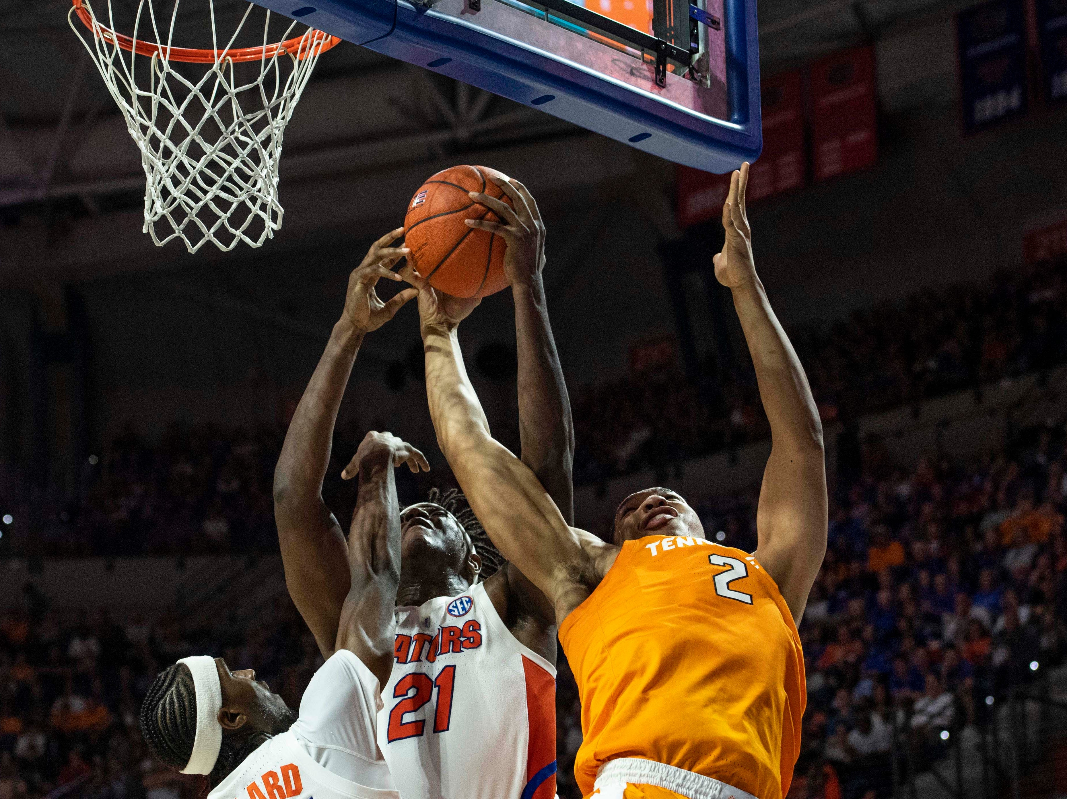Tennessee Volunteers forward Grant Williams (2) and Florida Gators forward Dontay Bassett (21) and guard Deaundrae Ballard (24) fight for a rebound on Jan. 12, 2019.