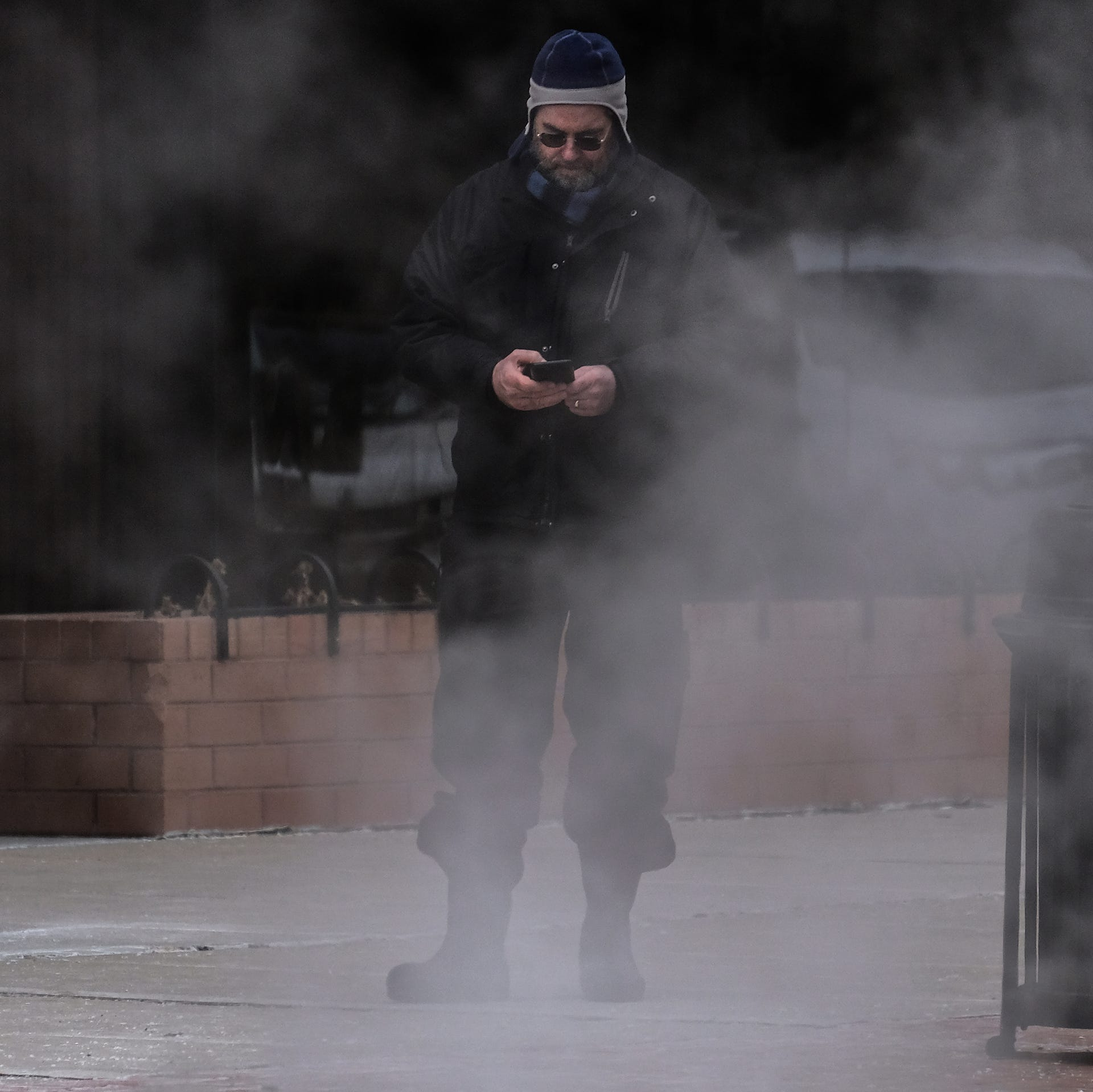 Steam rose from a vent Saturday afternoon in downtown Lansing into the cold air that partially obscured a man using his phone. The weather forecast this week calls for continued cold temperatures with lows this weekend in the single digits.