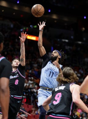 Memphis Grizzlies guard Mike Conley (11) shoots and scores against Miami Heat guard Tyler Johnson in the first half of an NBA basketball game on Saturday, Jan. 12, 2019, in Miami. (AP Photo/Brynn Anderson)