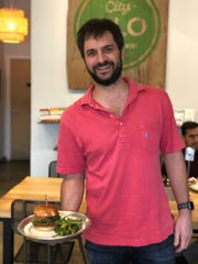Scott Tashie, owner of City Silo, brings their popular Silo Veggie Burger to a table.