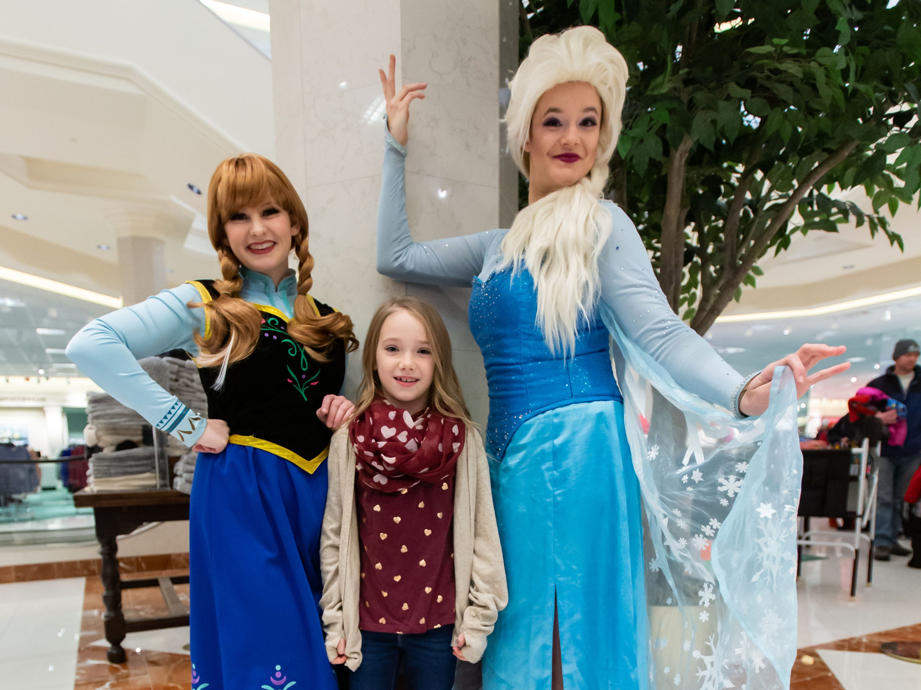 """Brinley O'Boyle, 7, of Milwaukee poses for a photo with the """"Frozen"""" princesses, Elsa and Anna, inside the Von Maur department store during Winter Fest at The Corners of Brookfield on Saturday, Jan. 12, 2019. The event included the Wisconsin State Ice Carving Championships, a screening of the movie """"Frozen"""", face painting, a caricature artist and much more."""