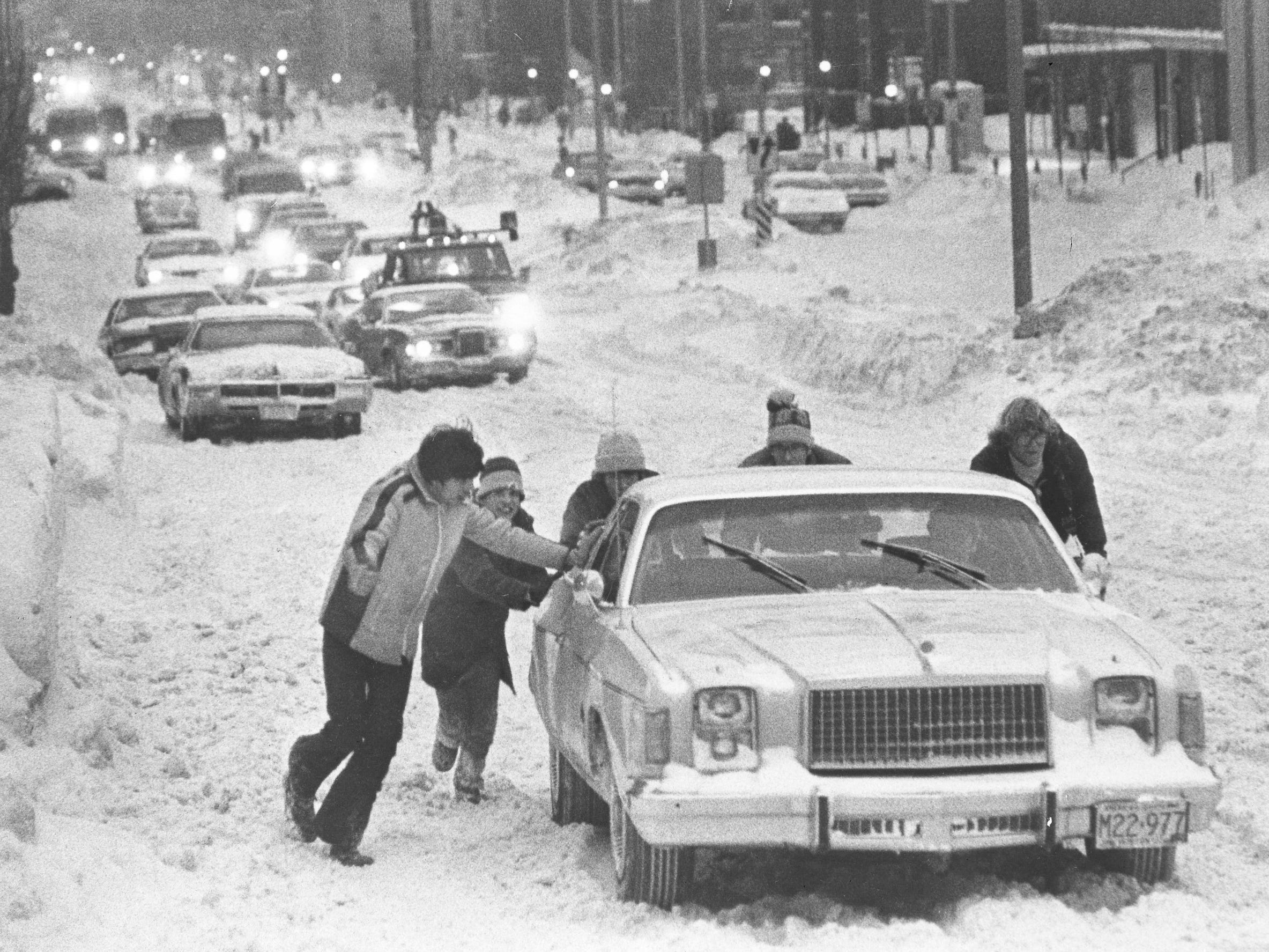 It takes a group effort to get this car back on track on Wisconsin Avenue at North 13th Street during a blizzard on Jan. 24, 1979. Milwaukee was hit with three double-digit snowstorms in less than four weeks that winter. This photo was published in the Jan. 25, 1979, Milwaukee Journal.
