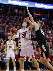 Wisconsin's Ethan Happ works against Purdue's Matt Haarms during their game Friday in Madison. Purdue won, 84-80, in overtime.