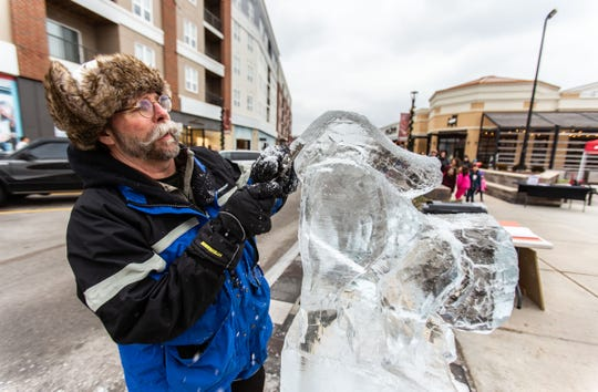 Mike Austin of Burlington competes in the Wisconsin State Ice Carving Championships held during Winter Fest at The Corners of Brookfield on Saturday, Jan. 12, 2019. Those ear flaps come down when it's super cold.