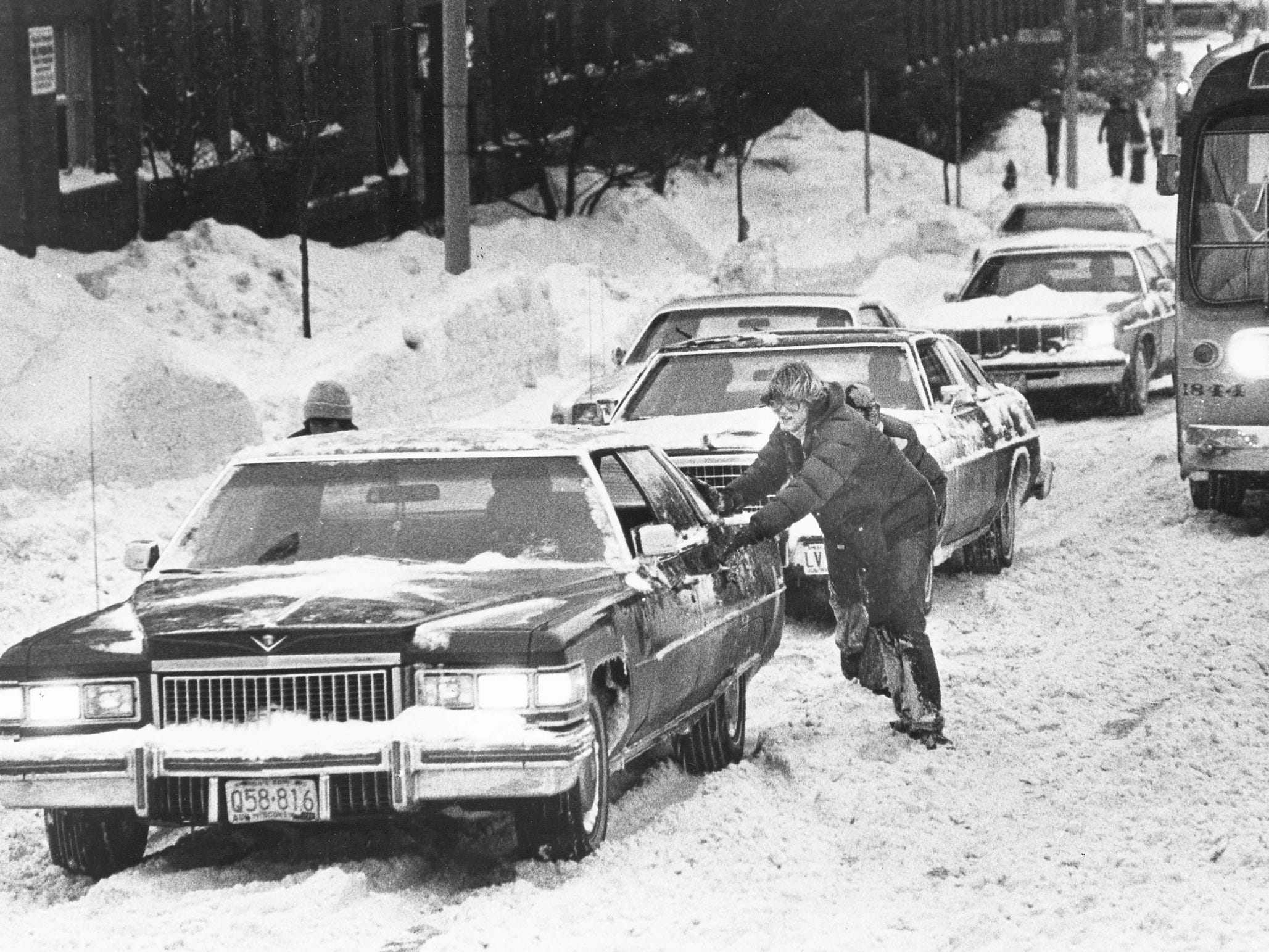 A driver gets help pushing a car out of a sticky spot on Wisconsin Avenue during a snowstorm in Milwaukee in this undated photo from January 1979.
