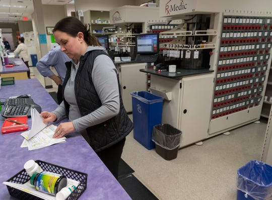 Pharmacy technician Megan Rasmussen works in the pharmacy in the Community Health Services clinic on the Oneida Indian Reservation in Oneida. The pharmacy, which fills about 1,000 prescriptions each day, is part of the clinic that receives about $20 million annually in federal funding.  Behind her are two automated dispensing systems for 450 of the most commonly prescribed medications.