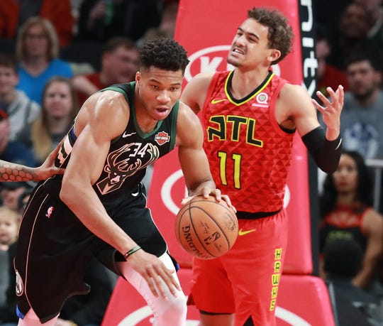 Bucks forward Giannis Antetokounmpo comes away with a defensive rebound as Hawks guard Trae Young reacts Sunday at State Farm Arena in Atlanta.