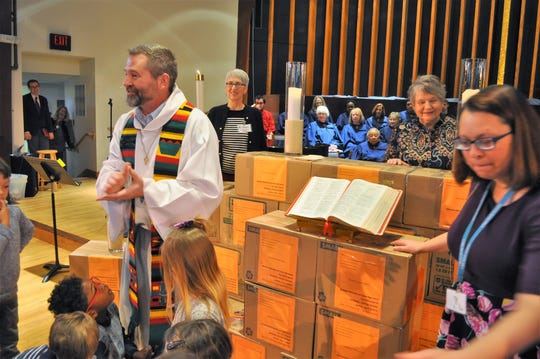 The Rev. Matt Hadley blesses 36 boxes of books during a church service on Sunday, Jan. 13, at United Methodist Church of Whitefish Bay. The church plans to ship the books to a school in Ghana.