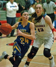 Mountain Home's Emma Martin drives past Paragould's Blythe Benefield on Friday night.