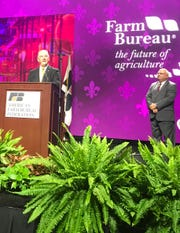 Gov. John Bel Edwards addresses the American Farm Bureau Convention Sunday in New Orleans as Louisiana Farm Bureau President Ronnie Anderson looks on.