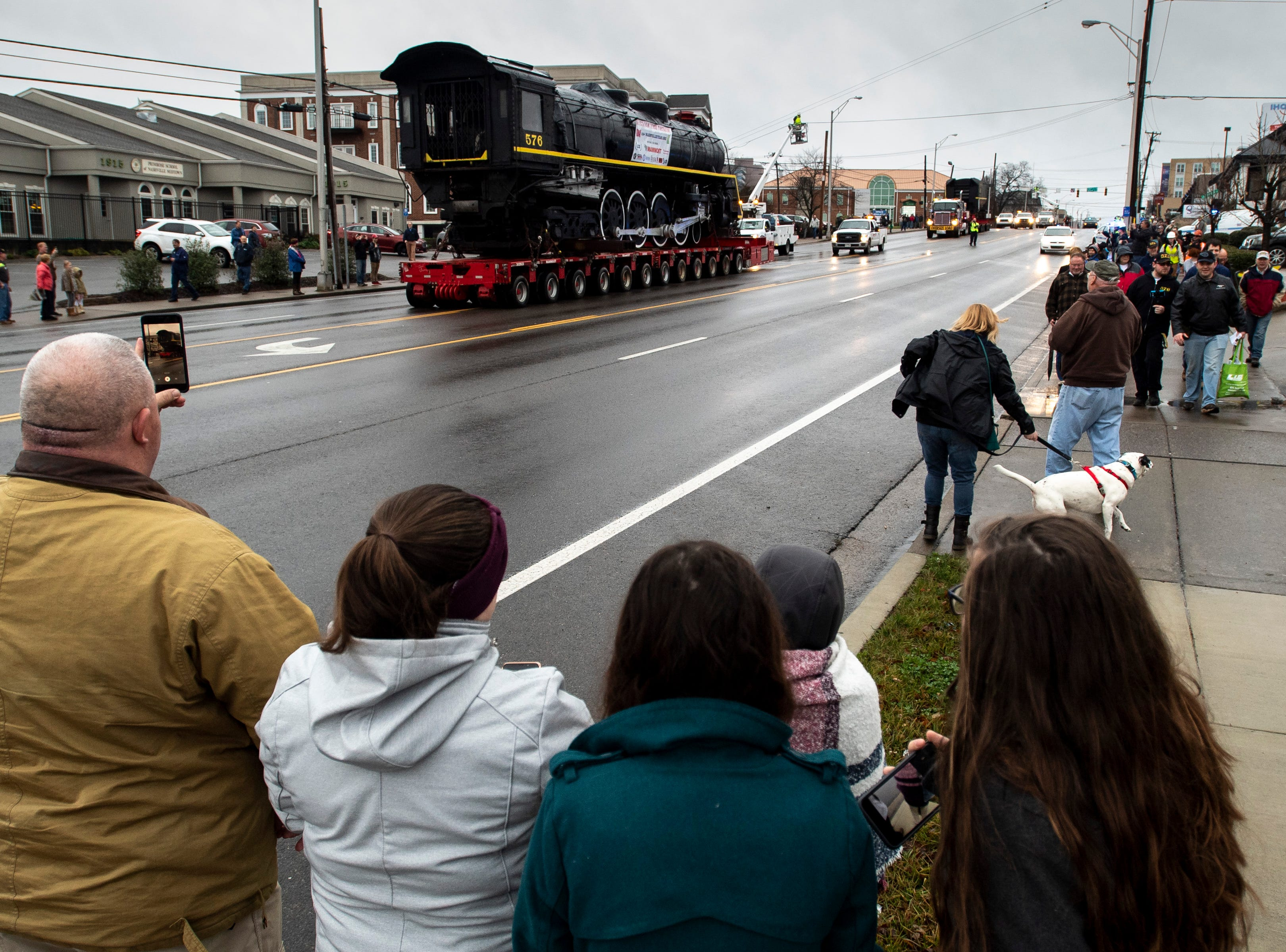 Spectators watch as former Nashville, Chattanooga & St. Louis Railway steam locomotive No. 576 is moved down Charlotte Ave. in Nashville, Tenn., Sunday, Jan. 13, 2019. The train, which will be restored to working condition over approximately four years, has been on display in Centennial Park since 1953.