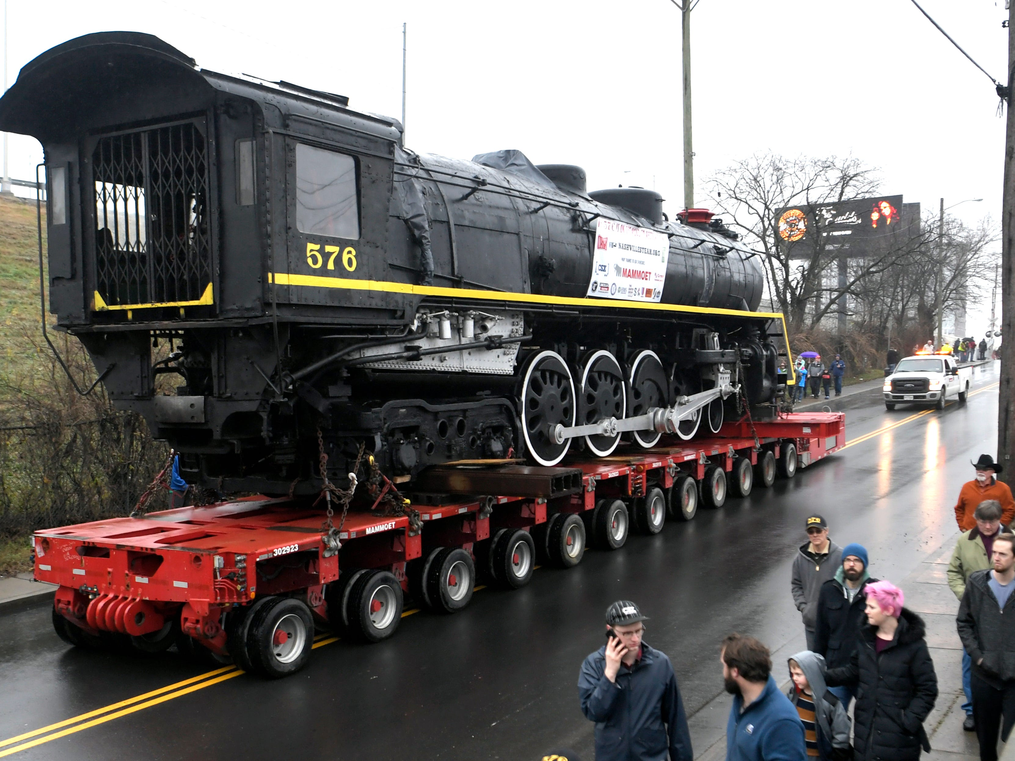 People walk with locomotive  No. 576 as it is being transported down 12th Ave North in Nashville on Sunday, Jan.  13, 2019.  The locomotive has been on display in Centennial Park for 65 years.