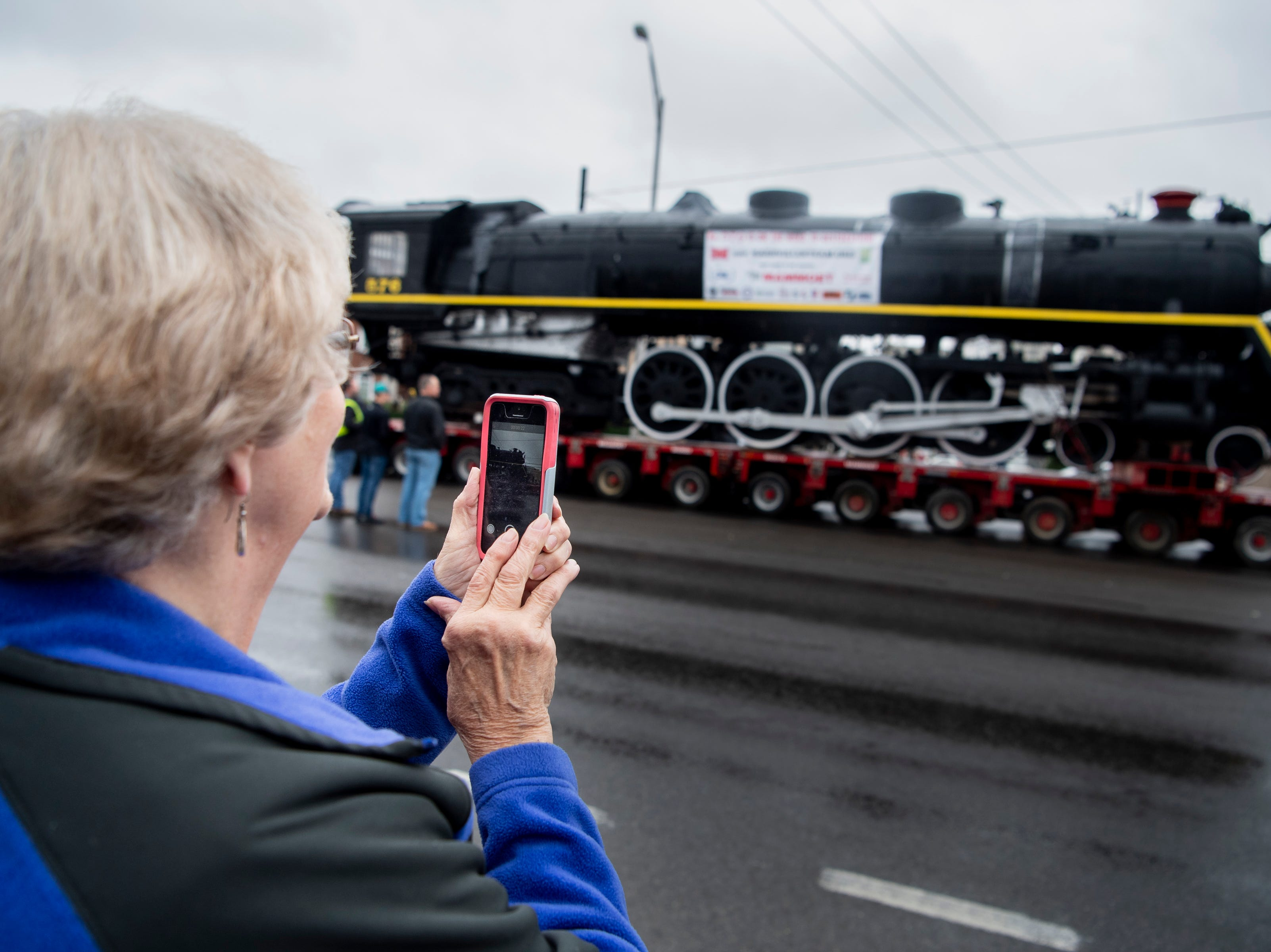 Barbara Cox, of Nashville, takes a picture as former Nashville, Chattanooga & St. Louis Railway steam locomotive No. 576 is moved down Charlotte Ave. in Nashville, Tenn., Sunday, Jan. 13, 2019. The train, which will be restored to working condition over approximately four years, has been on display in Centennial Park since 1953.