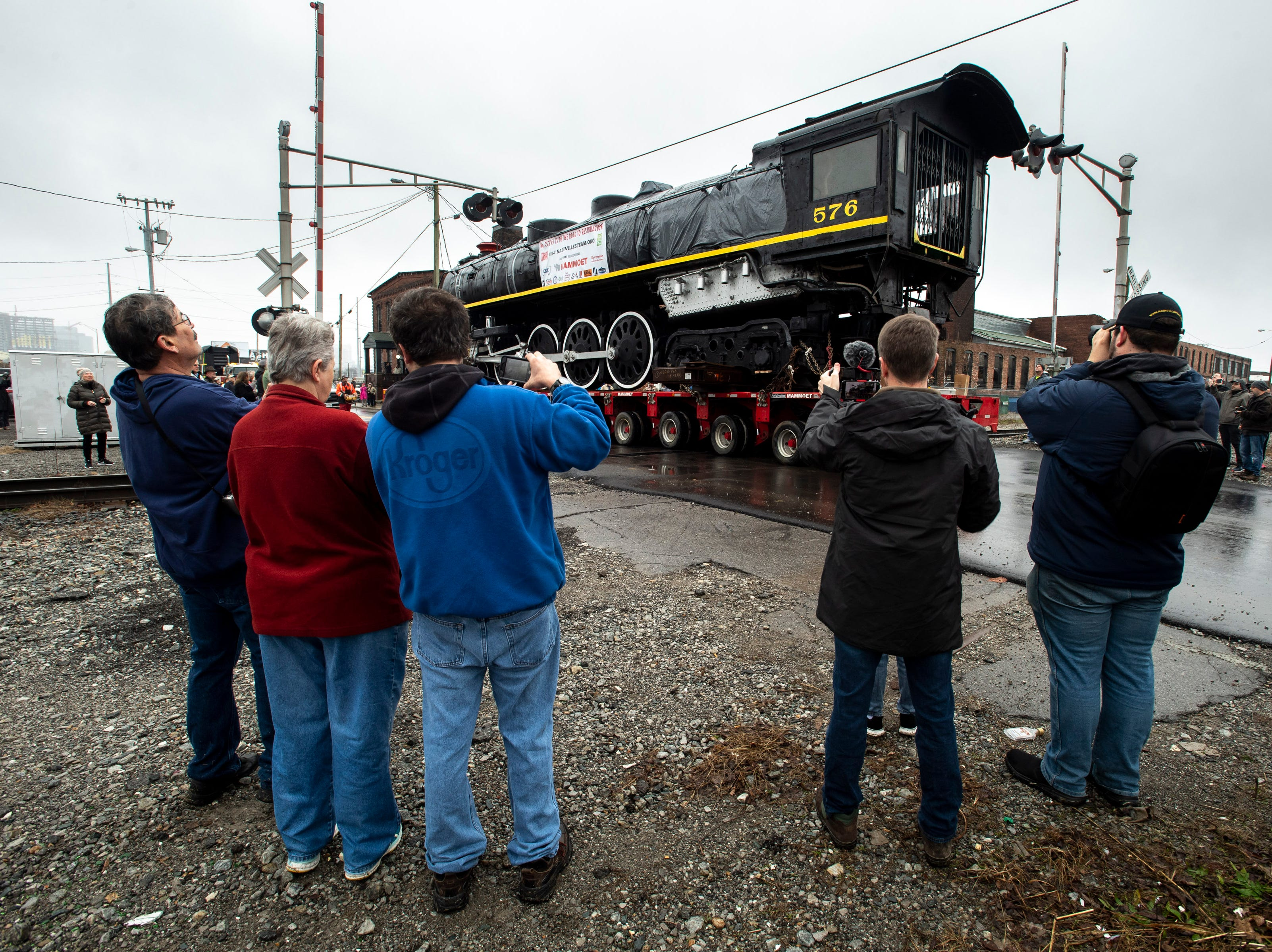 Spectators watch as former Nashville, Chattanooga & St. Louis Railway steam locomotive No. 576 is moved down 12th Ave. North in Nashville, Tenn., Sunday, Jan. 13, 2019. The train, which will be restored to working condition over approximately four years, has been on display in Centennial Park since 1953.