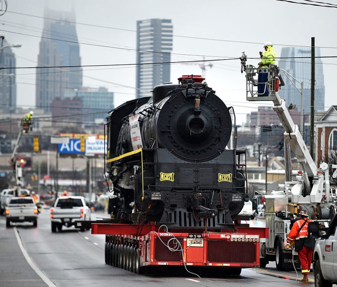 Powerlines are lifted to make room to transport locomotive No. 576 down Charlotte Ave. in Nashville on Sunday,  Jan. 13, 2019.  The locomotive has been on display in Centennial Park for 65 years and is being relocated for a restoration project.