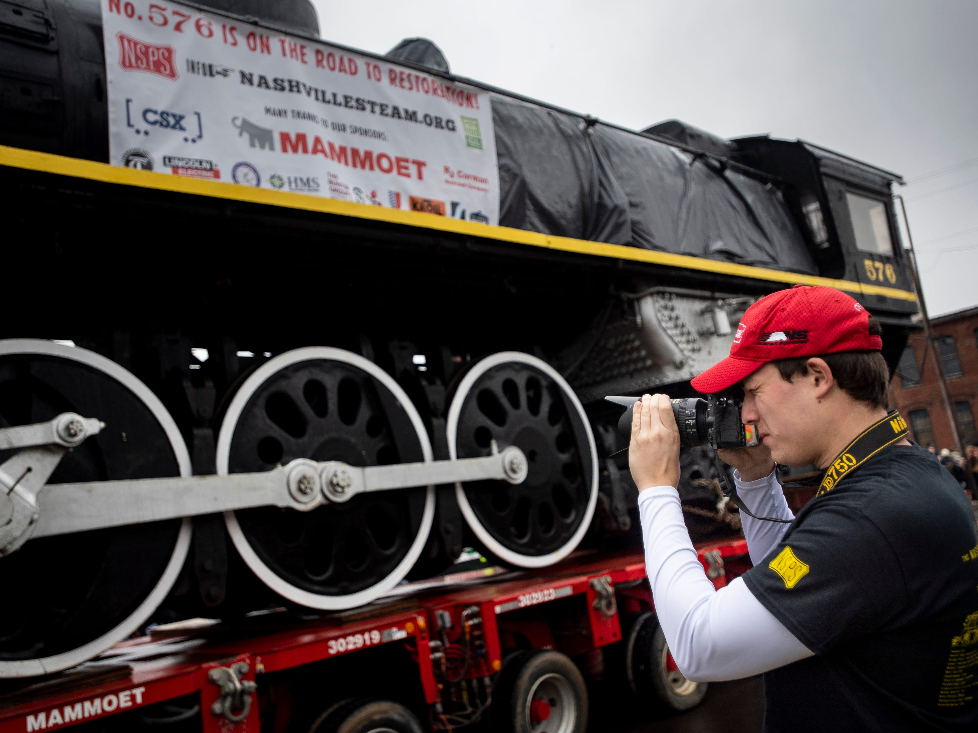Joseph Randall, of Kennesaw, Ga., takes pictures as former Nashville, Chattanooga & St. Louis Railway steam locomotive No. 576 is moved down 12th Ave. North in Nashville, Tenn., Sunday, Jan. 13, 2019. The train, which will be restored to working condition over approximately four years, has been on display in Centennial Park since 1953.