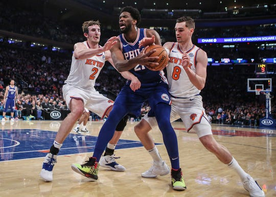 Philadelphia 76ers center Joel Embid (21) fights for a loose ball with New York Knicks forwards Luke Kornet (2) and Mario Hezonja (8) in the second quarter at Madison Square Garden.