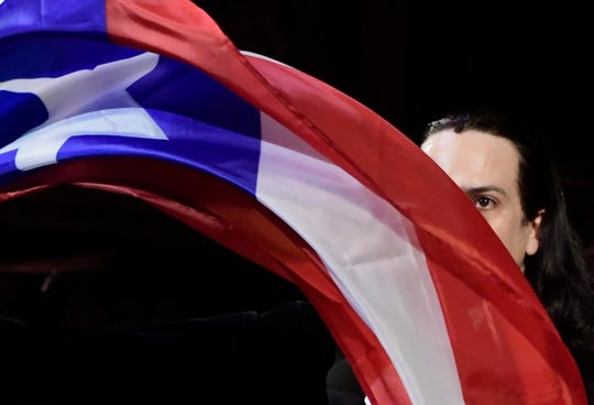 Lin-Manuel Miranda, composer and creator of the award-winning Broadway musical, Hamilton, proudly waves a Puerto Rican flag after receiving a standing ovation at the end of the play's premiere held at the Santurce Fine Arts Center, in San Juan, Puerto Rico, Friday, Jan. 11, 2019. The musical is set to run for two weeks and will raise money for local arts programs.