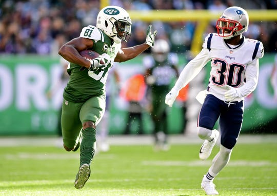 EAST RUTHERFORD, NEW JERSEY - NOVEMBER 25: Quincy Enunwa #81 of the New York Jets is pursued by Jason McCourty #30 of the New England Patriots during the first half at MetLife Stadium on November 25, 2018 in East Rutherford, New Jersey.