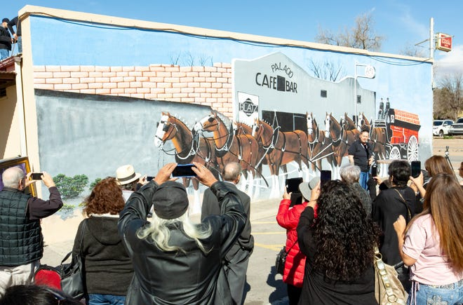 Many gather for the public unveiling of a mural depicting Budweiser Clydesdale horses at Palacio Bar on Sunday, Jan. 13, 2019, in Mesilla, New Mexico.