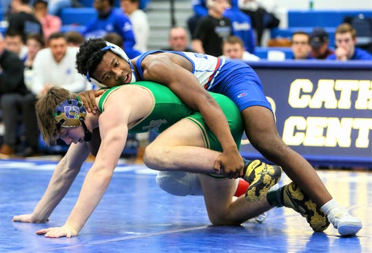 Catholic Central's Kevon Davenport (top) rides out Cathedral's Elliot Rodgers en route to 6-2 decision at 152 pounds.