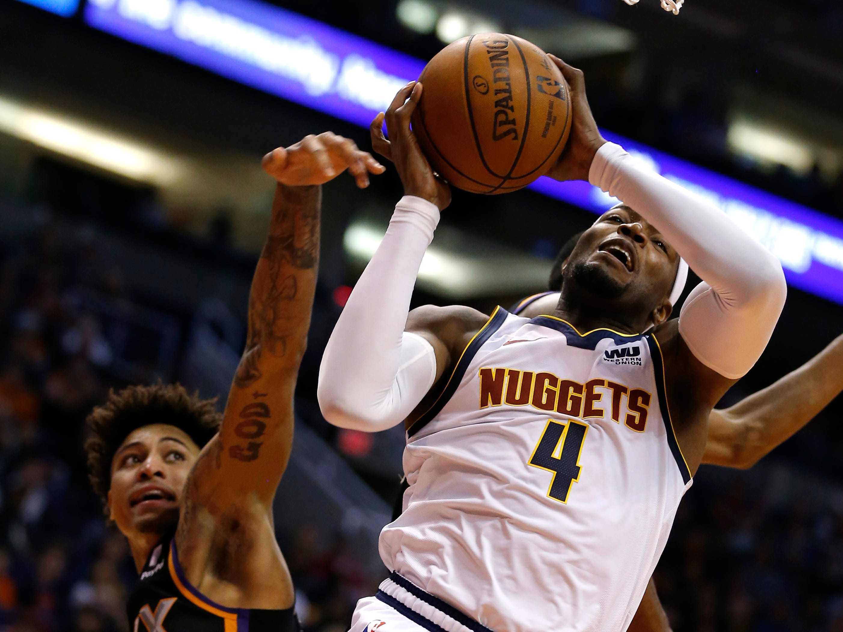 Denver Nuggets forward Paul Millsap (4) drives past Phoenix Suns forward Kelly Oubre Jr., Jan. 12, 2019, in Phoenix. (AP Photo/Rick Scuteri)