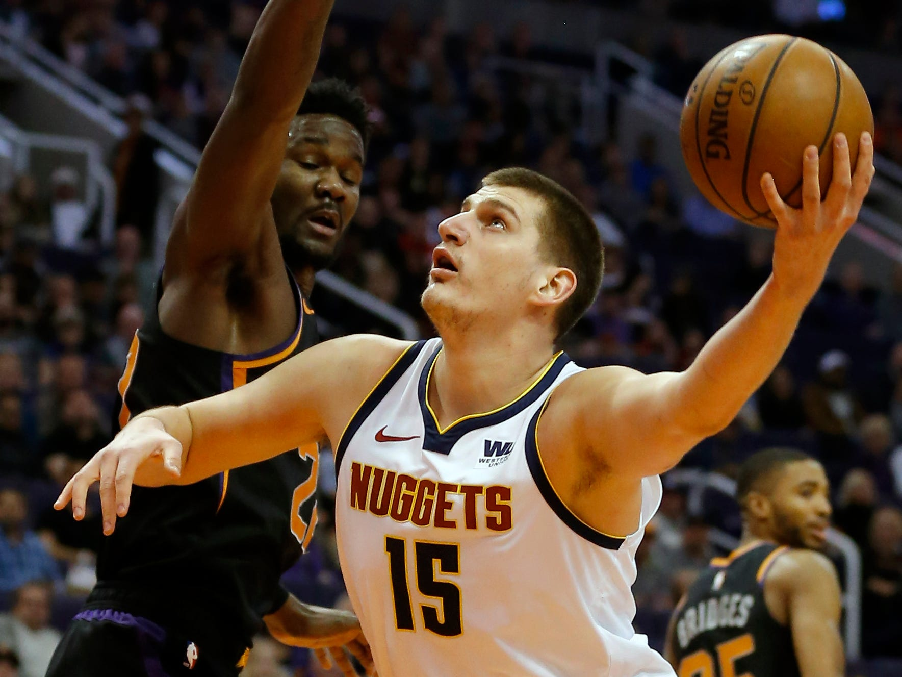 Denver Nuggets center Nikola Jokic (15) shoots around Phoenix Suns center Deandre Ayton, Saturday, Jan. 12, 2019, in Phoenix. (AP Photo/Rick Scuteri)