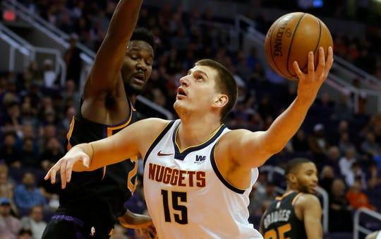Denver Nuggets center Nikola Jokic (15) shoots around Phoenix Suns center Deandre Ayton, Saturday, Jan. 12, 2019, in Phoenix. (AP Photo/Rick Scuteri)