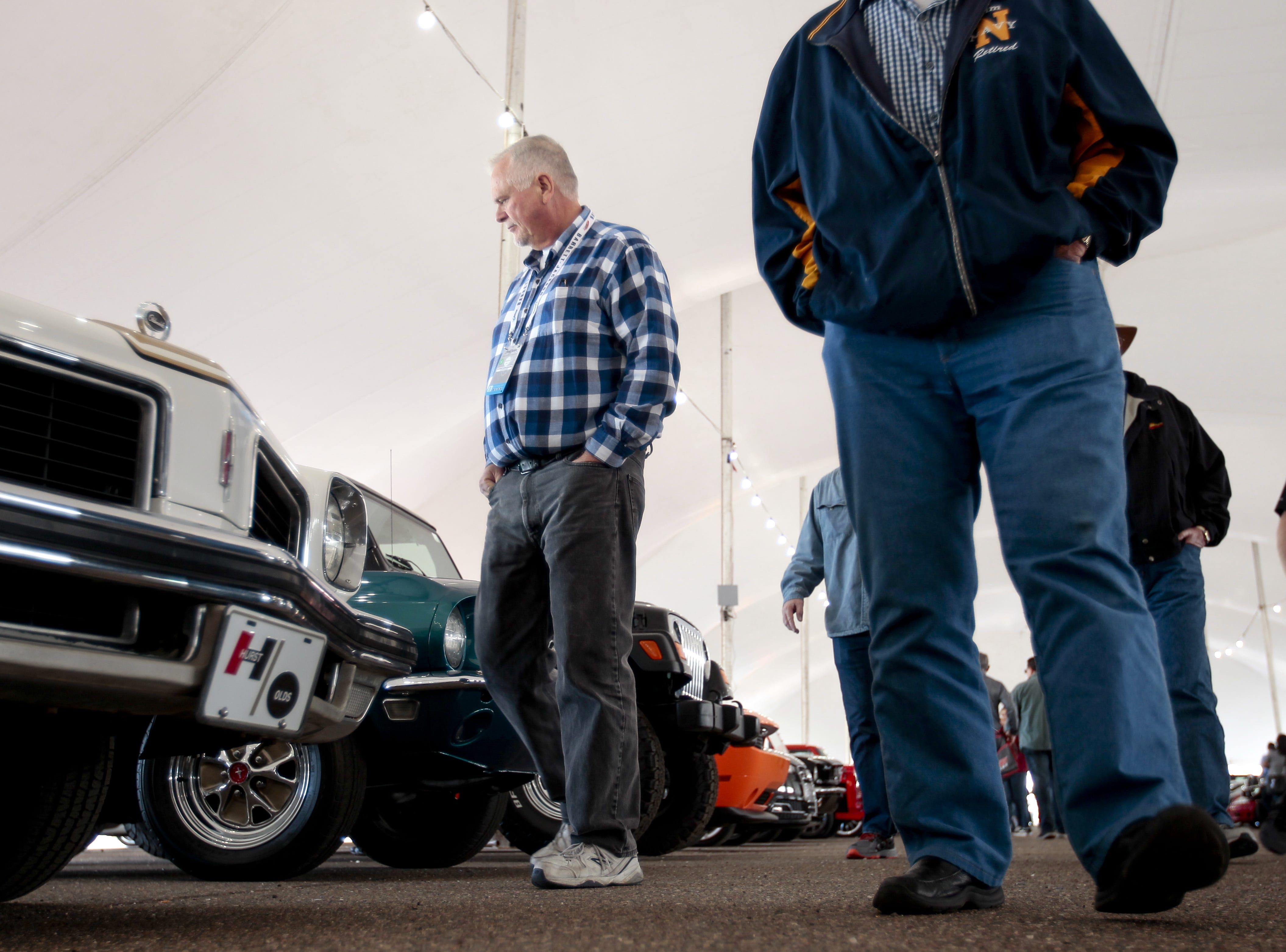 Visitors look at cars in the tents of the Barrett-Jackson Car Auction on Jan. 12, the first day of the event.