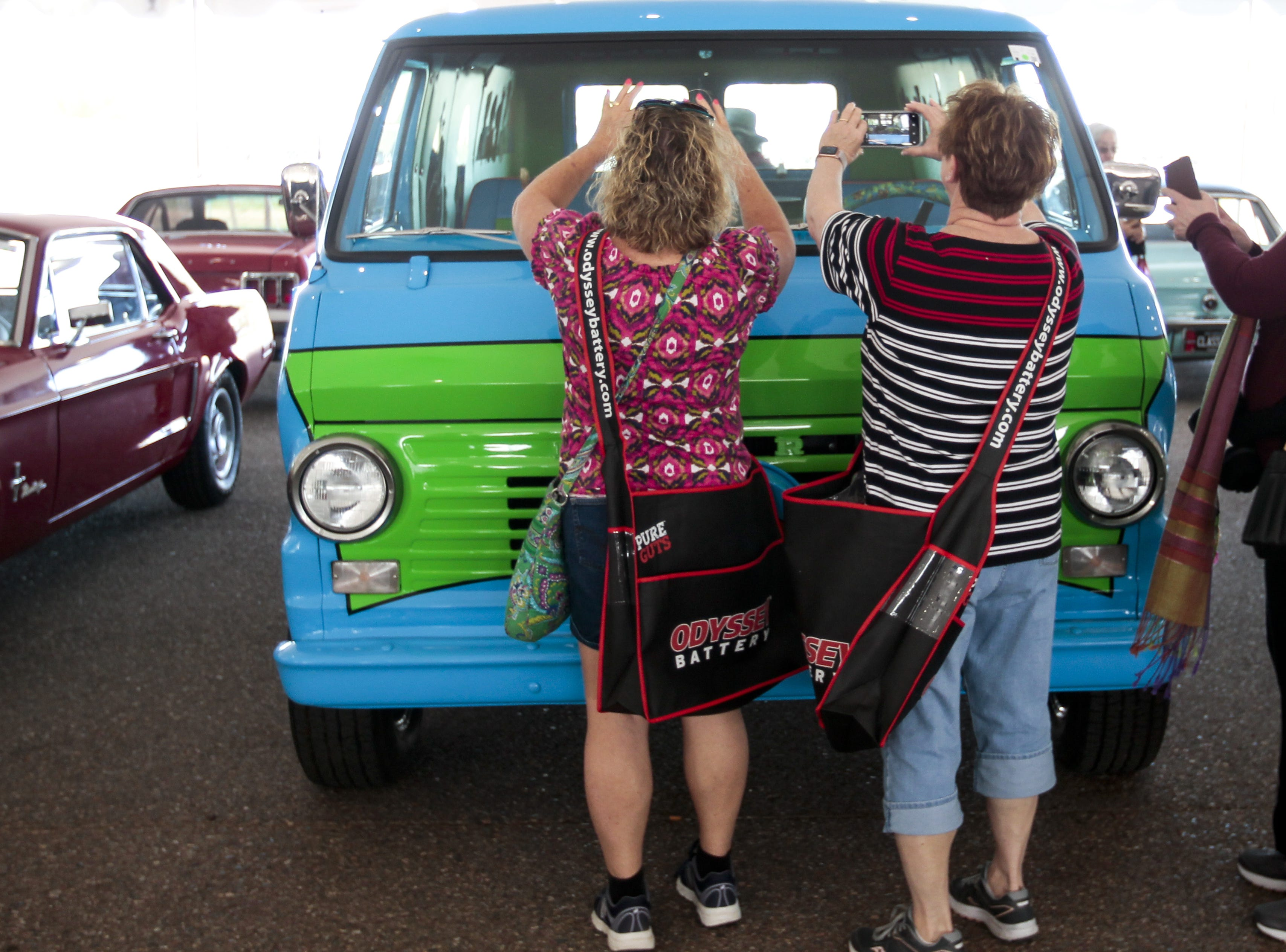 Bev Deckard, left, and Susie White take a photo of a van decked out to look like the Mystery Machine from Scooby Doo at the Barrett-Jackson Car Auction on Jan. 12, the first day of the event.