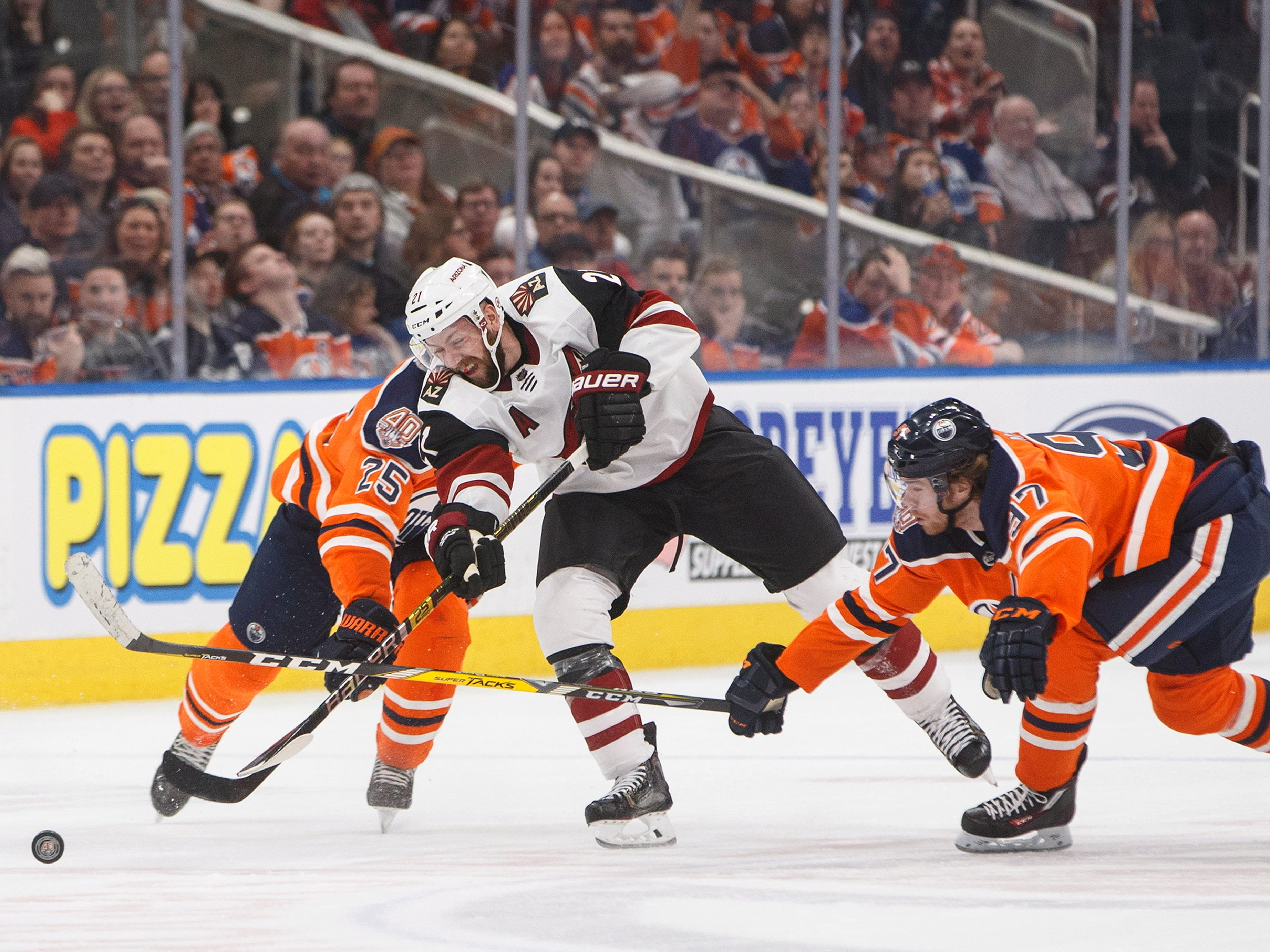 Arizona Coyotes' Derek Stepan (21) shoots as Edmonton Oilers' Darnell Nurse (25) and Connor McDavid (97) defend during the third period, Saturday, Jan. 12, 2019, in Edmonton Alberta. (Jason Franson/The Canadian Press via AP)