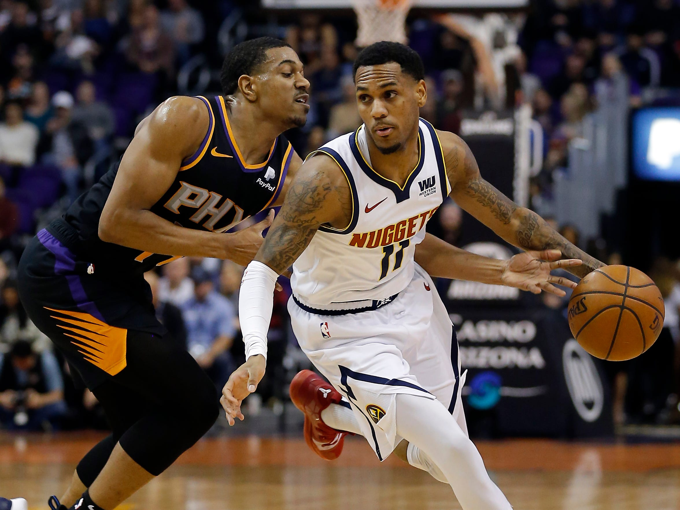 Denver Nuggets guard Monte Morris (11) drives past Phoenix Suns guard De'Anthony Melton, Saturday, Jan. 12, 2019, in Phoenix. (AP Photo/Rick Scuteri)