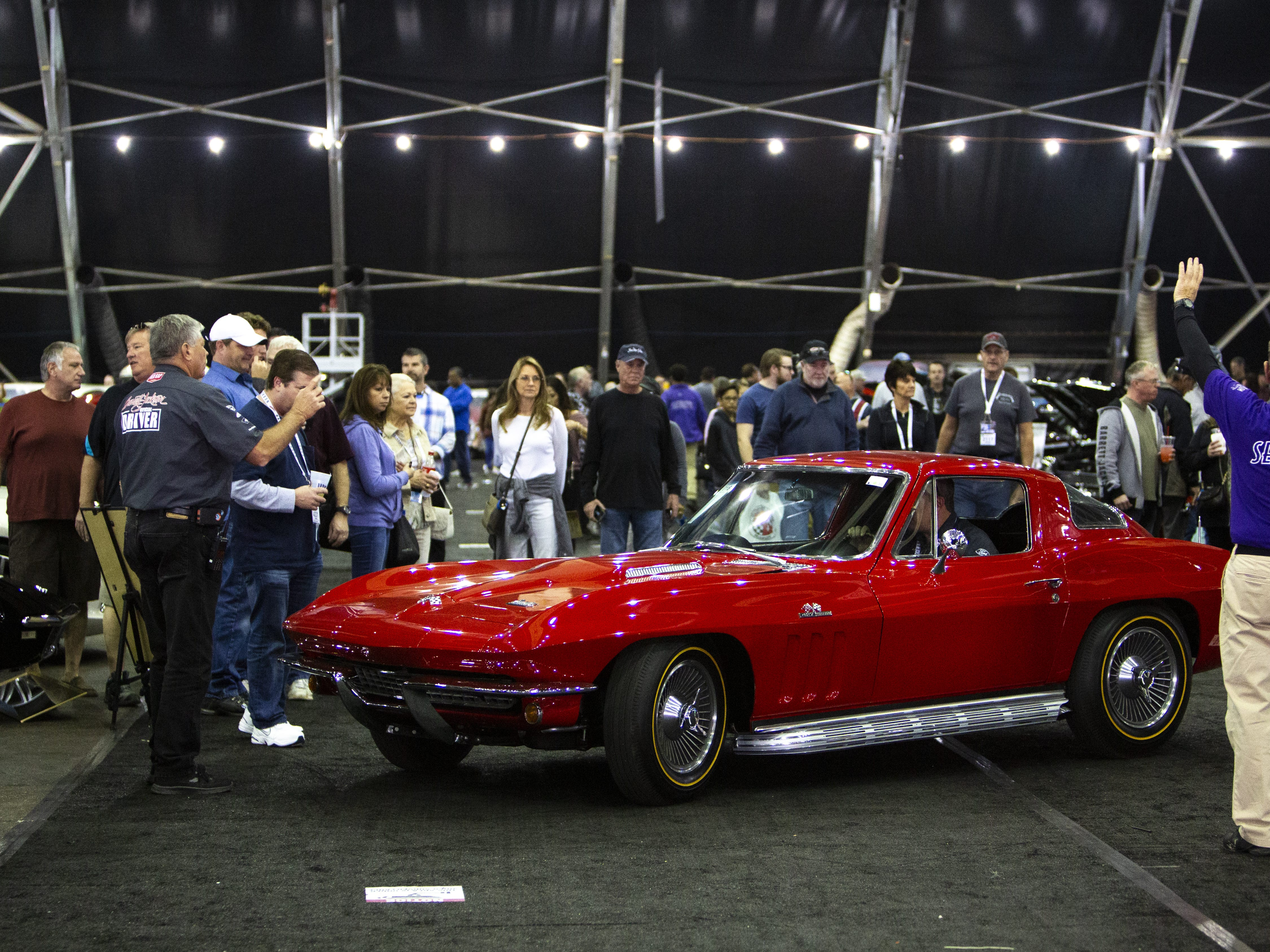 A crowd watches security direct a 1966 Chevrolet Corvette to its parking space inside the tents at the Barrett-Jackson Car Auction on Jan. 12, the first day of the event.